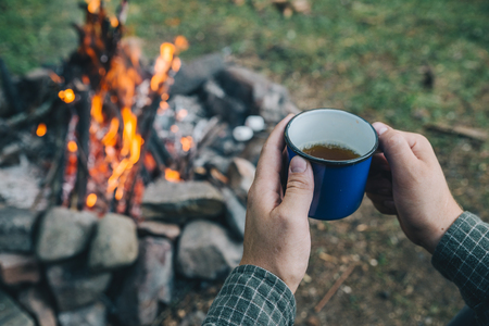 first point of view. man drinking tea in metal cup near camp fire. hiking