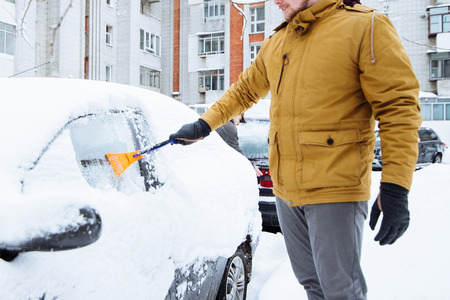 man cleaning car after snowstorm. streets covered snow Stockfoto