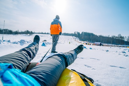 man pulling sleigh with friend. winter activity. snow tubing