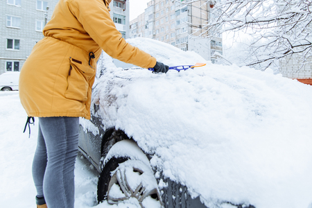 woman cleaning her car of snow after snowstorm. winter time