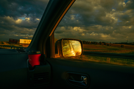 sunset reflection in car mirror on highway. road trip Stock Photo