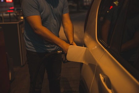 man fueling up the car in the evening on gas station Stock Photo