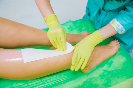 woman making sugaring in cosmetic center. epilation beauty concept. sexy legs Zdjęcie Seryjne