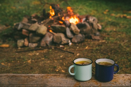 two metal cups with tea. fire on background. union with nature