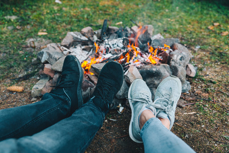 leg of two persons in front of camp fire. hiking Stock Photo