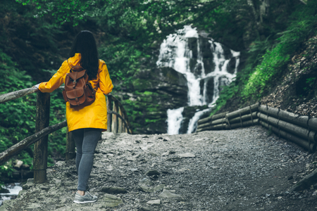 woman walking to waterfall in yellow raincoat. copy space