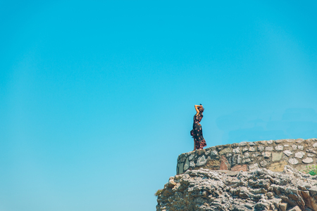 woman stand on the cliff in light dress at sunny day. freedom emotions Stock Photo