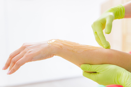 woman making sugaring in cosmetic center. epilation beauty concept. hands close up