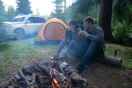 couple sitting near camp fire and drinking tea. tent and suv on background. union with nature Banco de Imagens