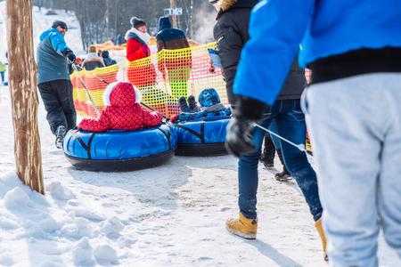 LVIV, UKRAINE - March 3, 2018: two kids ride in sleigh. snow tubing. winter activity Editorial