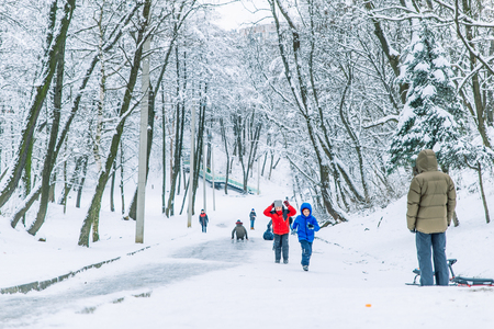 LVIV, UKRAINE - December 21, 2017: kids slide ice hill, playing outdoors at snowed winter day concept
