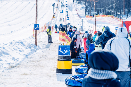 LVIV, UKRAINE - March 3, 2018: people in line to ride from snow hill. snow tubing. winter activity