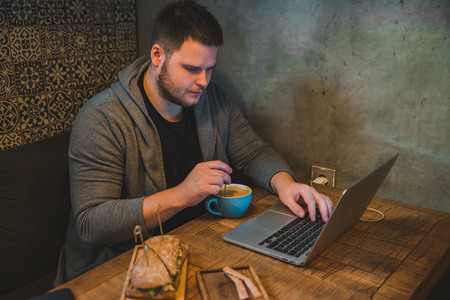 man working on laptop in cafe. breakfast sandwich and coffee concept