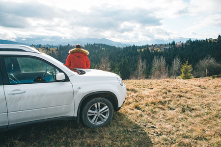 man lean on the car looking at beautiful view of mountains. off road concept. road trip 写真素材