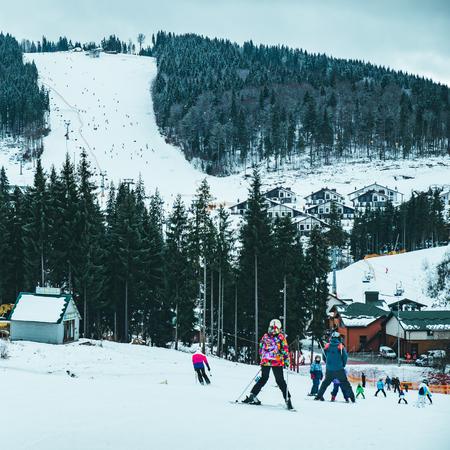 BUKOVEL, UKRAINE - December 9, 2018: people skiing from snowed hill. winter sport activity. vacation concept