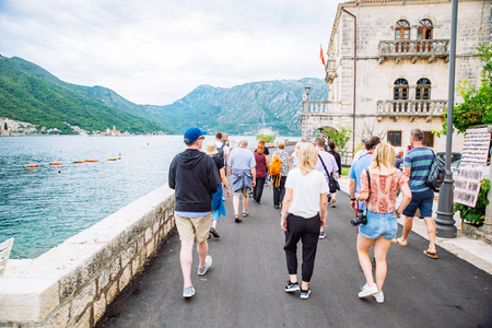 PERAST, MONTENEGRO - July 17, 2018: group of tourists walk by Perast town near adriatic sea. summer travel concept