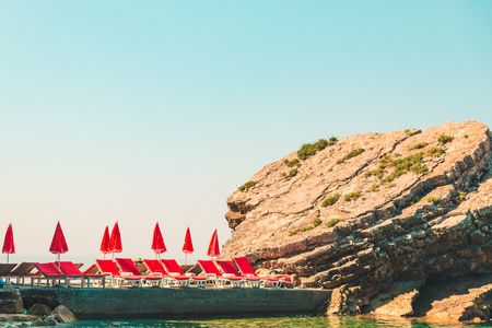 sun loungers with umbrella at rocky seaside. summer vacation
