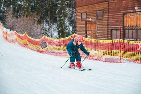 BUKOVEL, UKRAINE - December 9, 2018: little kid skiing at snowed hill by him self. winter sport activity