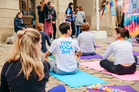 LVIV, UKRAINE - June 29, 2018: lviv yoga day in center of city. people practice yoga at city street.