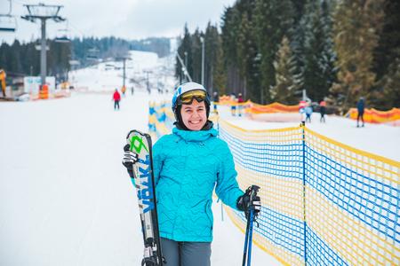 BUKOVEL, UKRAINE - December 9, 2018: young adult woman in sport ski wear in helmet and eyeglasses. ski resort on background. winter activity Editorial