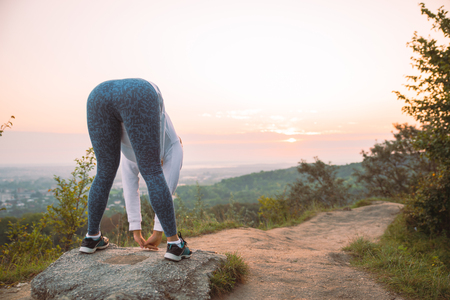 woman do exercise in the morning on sunrise on top of the hill above the city. lifestyle concept