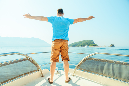 man standing with rising hand at nose of the boat. summer vacation
