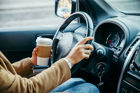 woman hands close up. driving car. view from inside. drinking coffee. road trip