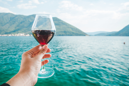 woman hand holding glass of red wine mountains and seaside on background