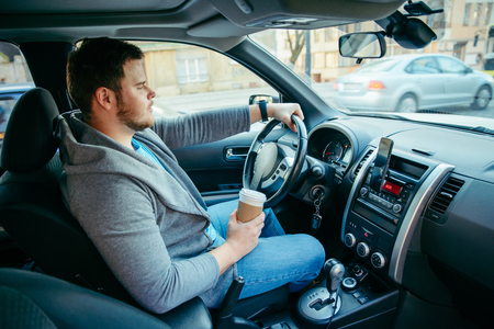 man driving car in traffic and drinking cup of coffee. lifestyle