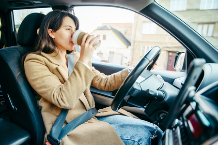 young pretty woman driving car while drinking cup of coffee. lifestyle