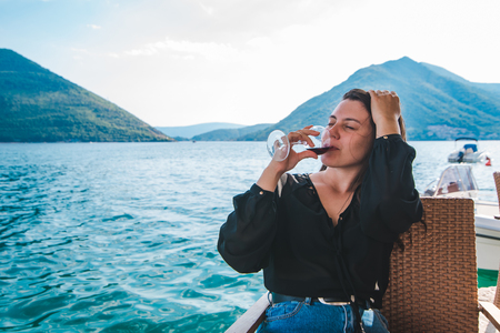 smiling young woman drinking red wine at seaside with beautiful mountains view. resting in cafe