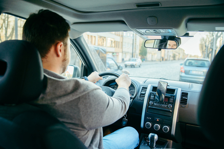 young adult man driving car by city streets using phone as navigation. lifestyle