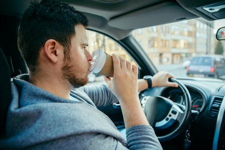 man driving car and drinking coffee. lifestyle