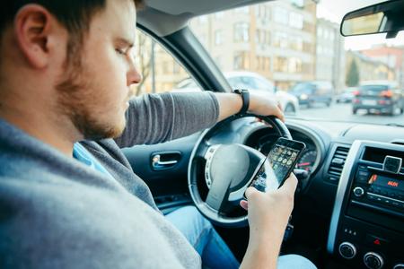 man hands on steering wheel using phone as navigator. road trip