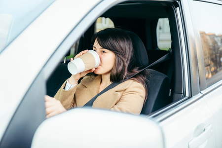 young woman driving car. safety belt. drinking coffee Stock Photo