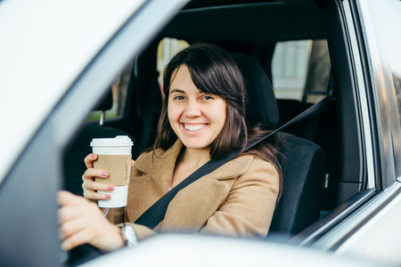 young smiling woman driving car. safety belt. drinking coffee