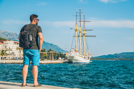 man standing at seaside with beautiful view of bay with big ship. summer time.