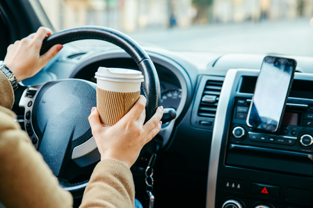 woman driving car and drinking coffee. phone navigation. lifestyle Stock Photo