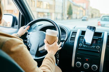 mujer conduciendo coche y tomando café. navegación del teléfono. estilo de vida