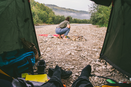couple resting at nature. camping. cooking on campfire. view from tent Stock Photo