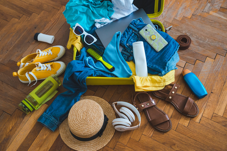 travel concept. yellow suitcase with different stuff around it. top view Imagens
