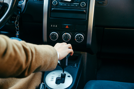 young woman hand on gear shift stick in car. road trip
