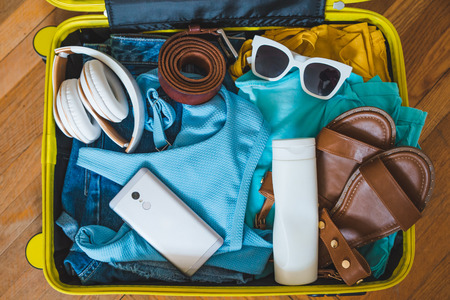 travel concept. yellow suitcase with different stuff around it. top view Stock Photo