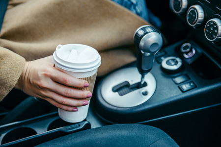 woman hand taking cup with coffee in car. close up. crop. morning energy. lifestyle Stock Photo