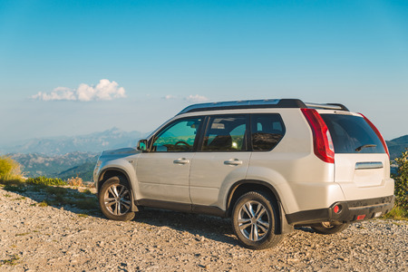 white suv car on the peak of the hill with mountains on background. car travel
