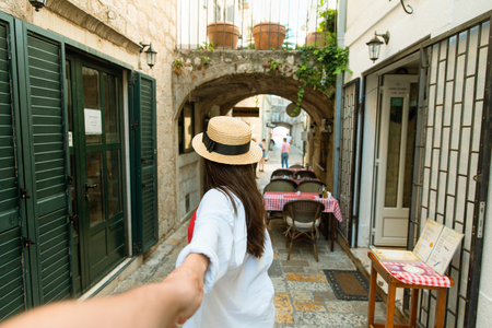 follow me concept. woman holding man hand in tight stone street of Budva. summer vacation
