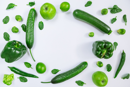 green vegetables and fruits on white background with copy space. overhead view