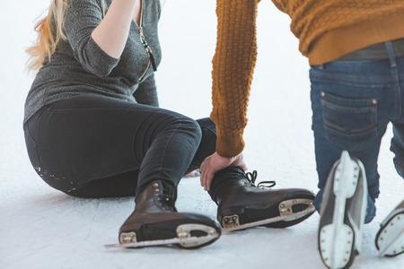 woman fall down while skating. man helping her. sport activities