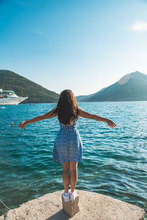 young pretty woman at the edge of the dock with beautiful view of mountains and sea with cruise liner. summer vacation travel
