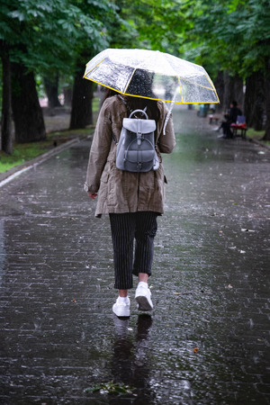 rainy weather. woman walking with umbrella by city park.